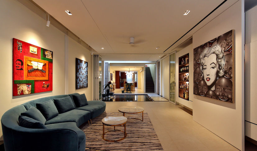 The living room that showcases Kan's art collection, whiskey bar and television concealed by the artwork (Photo: Samuel Isaac Chua/EdgeProp Singapore)