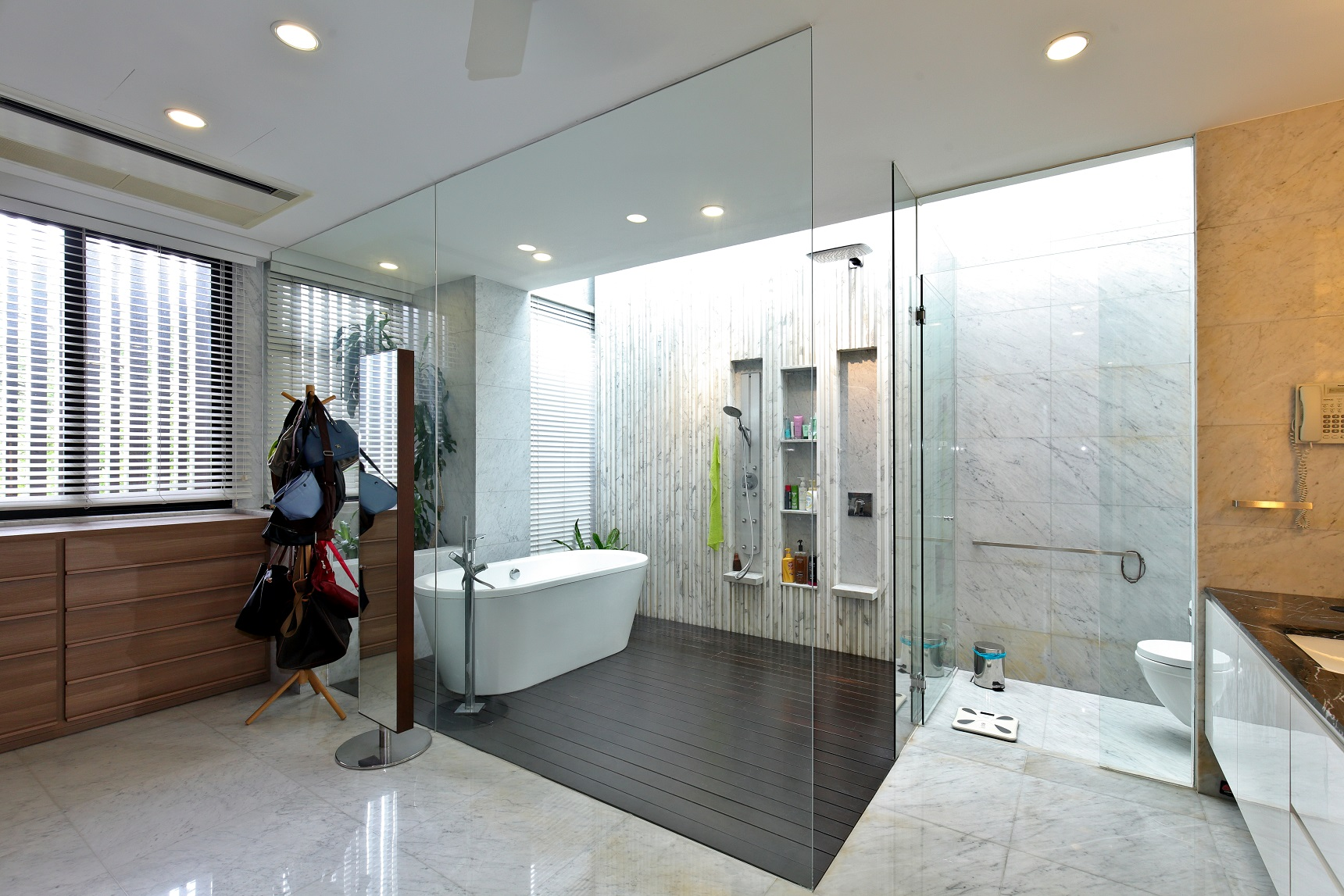 The master bathroom has a semi-open shower area, with chengal wood flooring and a feature wall of marble strips (Photo: Samuel Isaac Chua/EdgeProp Singapore)