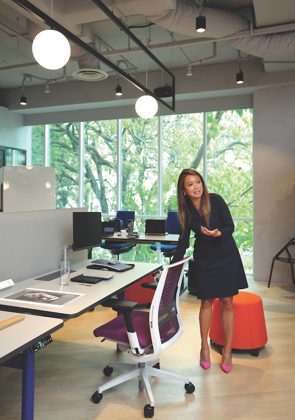 Giam demonstrating Steelcase's fittings (Credit: Samuel Isaac Chua/ The Edge Singapore)