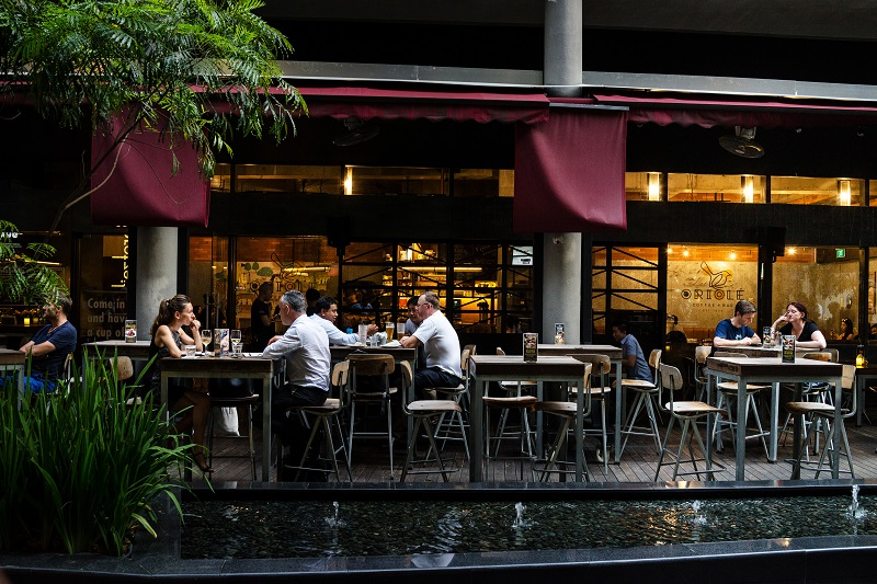 Customers sit at a bar on Orchard Road in Singapore, on Monday, June 5, 2017. - EDGEPROP SINGAPORE