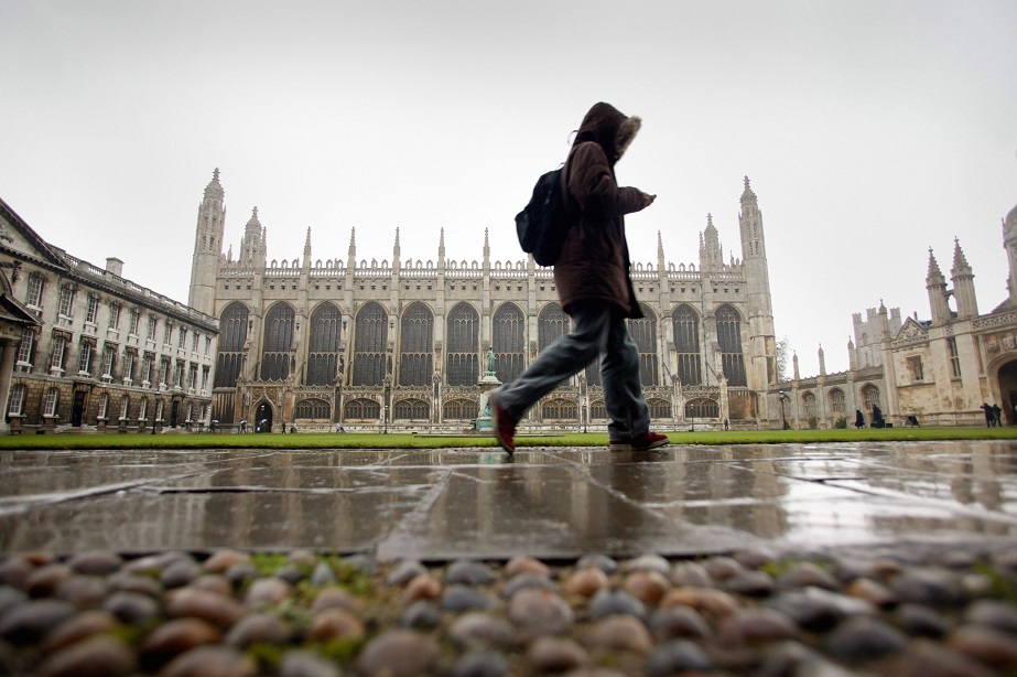 A student walks through the quadrangle of King's College, Cambridge. Photographer: Graham Barclay/Bloomberg News