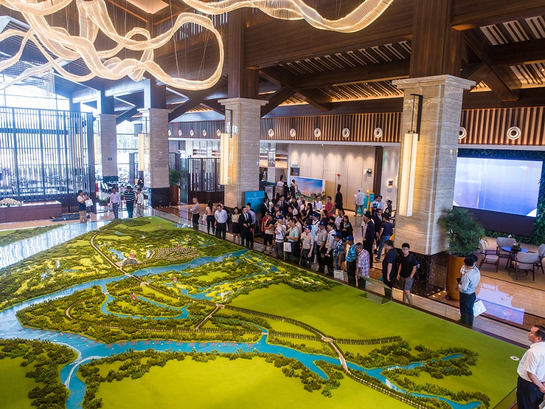 Guests look at a scale model of Forest City Golf Resort at the lobby of Forest City Golf Hotel